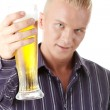 Happy young man holding a glass of beer - Stock Photo