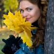 The beautiful girl with yellow leaves — Stok fotoğraf