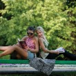 Two girls on a bench in park - Stock Photo