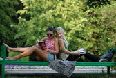 Two girls on a bench in park — Stock Photo