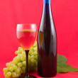 Wine and grapes on a red background — Stock Photo #1645592