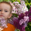 Stock Photo: Boy with a bouquet of lilacs