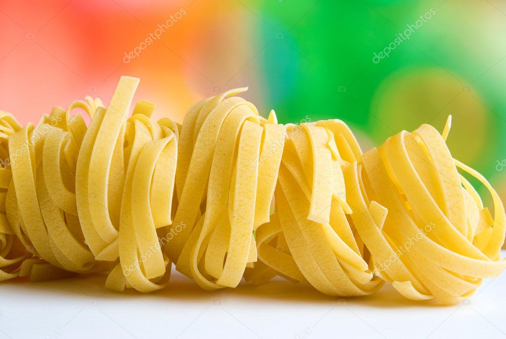 Row of raw dry nest pasta on colored background — Stock Photo #1789715
