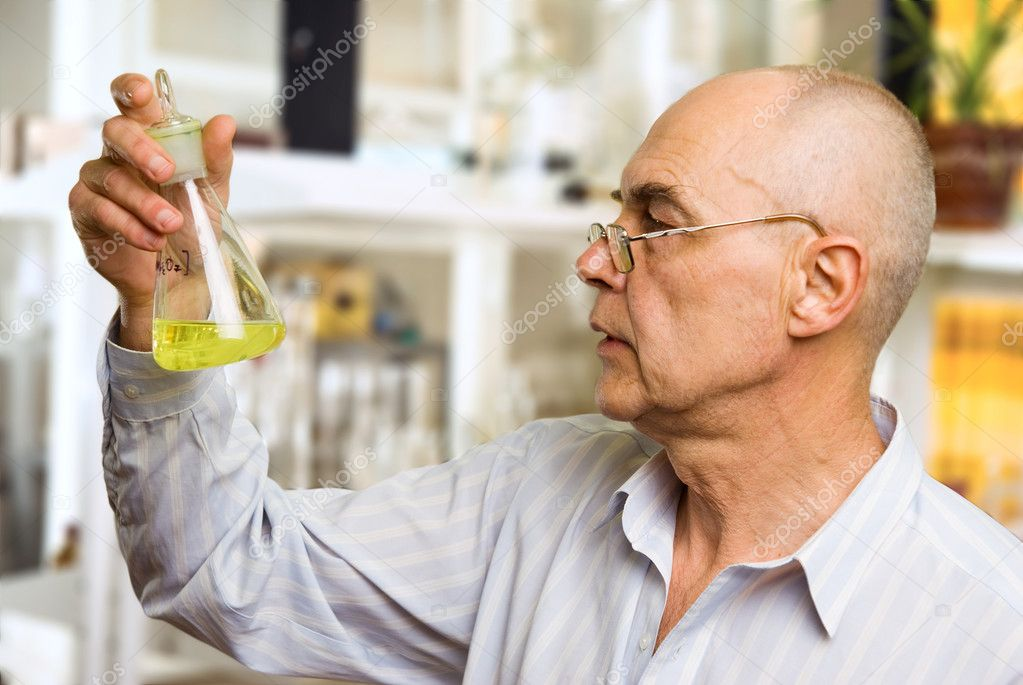 Scientist in the chemical lab examines a flask with a substance — Stock Photo #2324712