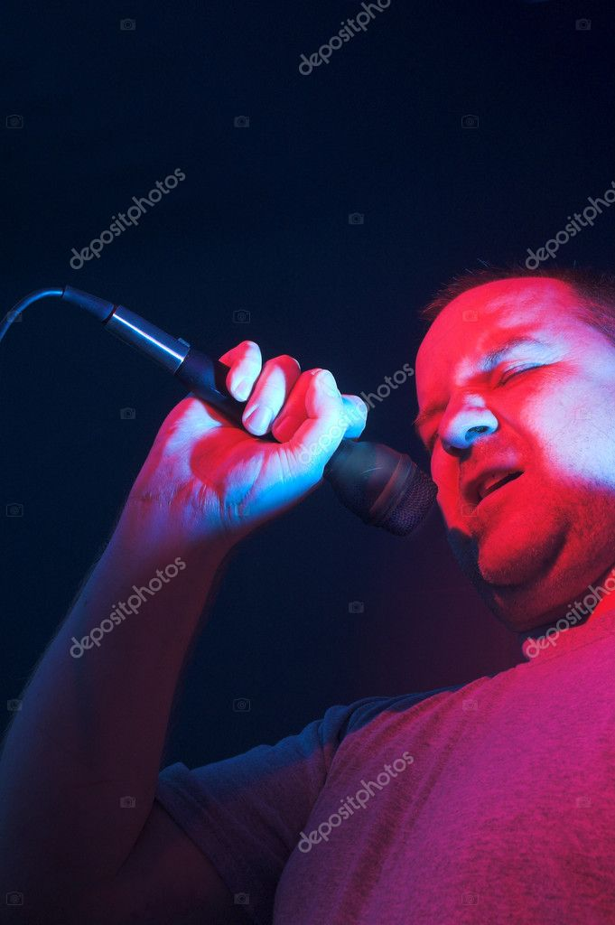 A man singing at a concert under stage lights. — Stock Photo #1700273