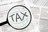 Federal tax forms under a magnifying glass. — Stock Photo
