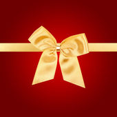 Gold Christmas bow on red card — 图库照片