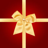 Gold Christmas bow on red card — Stock Photo
