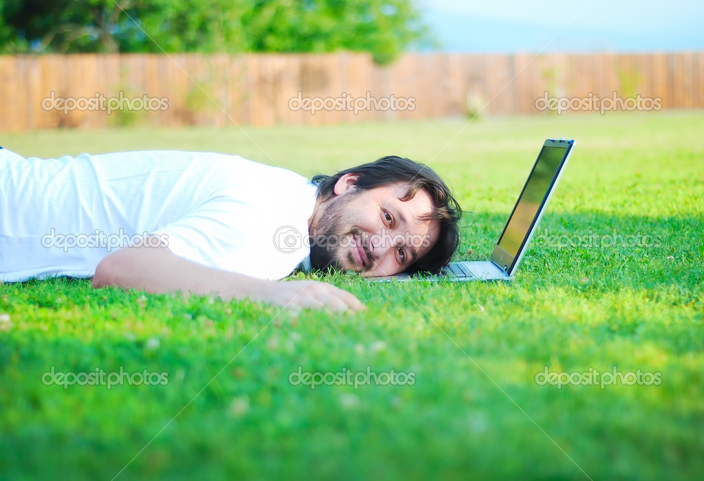 Happy young man on green meadow with laptop  — Stock Photo #1768318