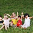 Happy children raising hands upwards - Stock Photo