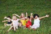 Happy children raising hands upwards — Stock Photo