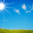 Sun in the cloudly sky over green grass — Stock Photo