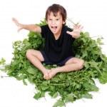 un simpatico ragazzino seduto sul congedo verde — Foto Stock