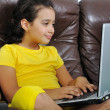 Beautiful girl in yellow reading on laptop — Stock Photo