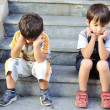 Two sad children on steps — Stock Photo