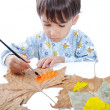A little sweet boy painting on leaves — Stockfoto