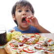 Cute little boy eating pizza on table, i - Stock Photo