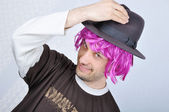 Young funny man with wig and hat — Stock Photo