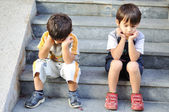 Two sad children on steps — Stockfoto