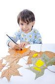 Um menino doce pintura em folhas — Fotografia Stock