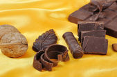 Chocolate, table, pieces, on golden back — Stock Photo