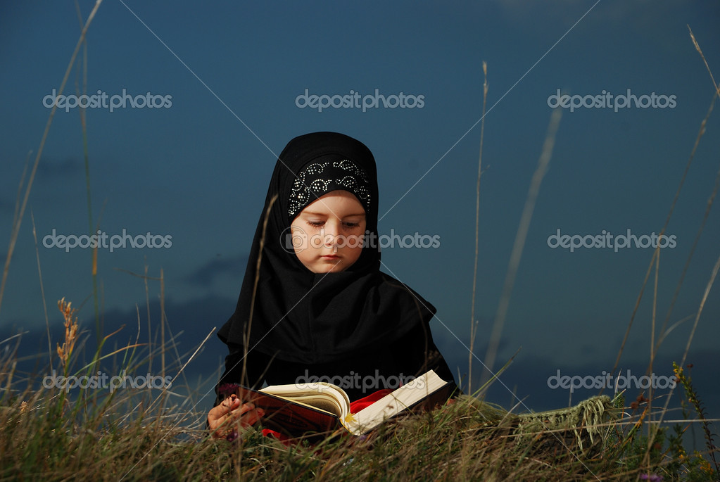 A little cute muslim girl reading holy book Koran outdoor — Stock Photo #1833390