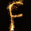 Letter F made of sparklers isolated — Stock Photo