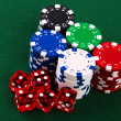 Stacks of casino chips and dice on green — Stock Photo