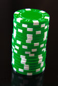 Green casino chips on black background — ストック写真