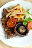 Steak with fries and salad — Stock Photo