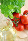 Tomatoes with basil and oil — Stock Photo