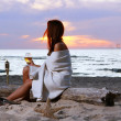 Stock Photo: Beautiful young womdrinking wine on beach