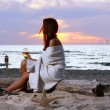 Beautiful young woman drinking wine on beach — Stock Photo
