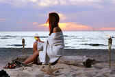 Beautiful young woman drinking wine on beach — Stock Photo