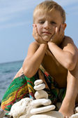 Child on beach building pyramid. — Stock Photo
