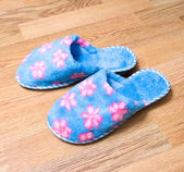 Fluffy domestic slippers on the parquet — 图库照片