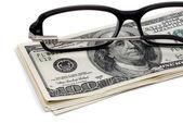 Glasses dollar bills over white. — Stock Photo