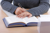 A young woman's hand writing on a writing pad — Stock Photo