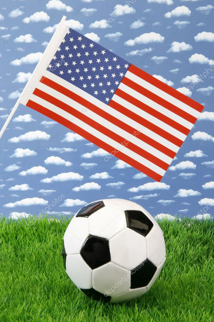 Soccerball on grass with american United States flag over sky background — Stock Photo #1646410
