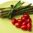 Asparagus ang grape tomatoes on plate — Stock Photo