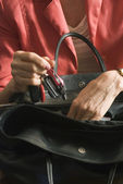 Woman hands looking in black woman bag — Stock Photo