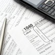 Mobile phone and pen on tax forms — Stock Photo