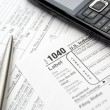 Mobile phone and pen on tax forms — Stockfoto