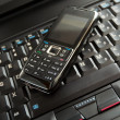 Stock Photo: Cell phone and laptop keyboard
