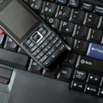 telefono cellulare e la tastiera del computer portatile — Foto Stock