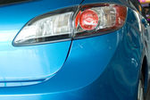 Modern red rear light of a blue car — Stock Photo