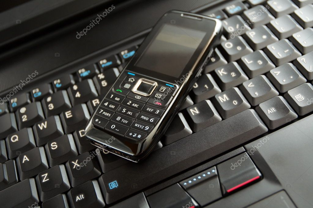 Black mobile phone on laptop keyboard as a wireless technology concept. — Stock Photo #2376934