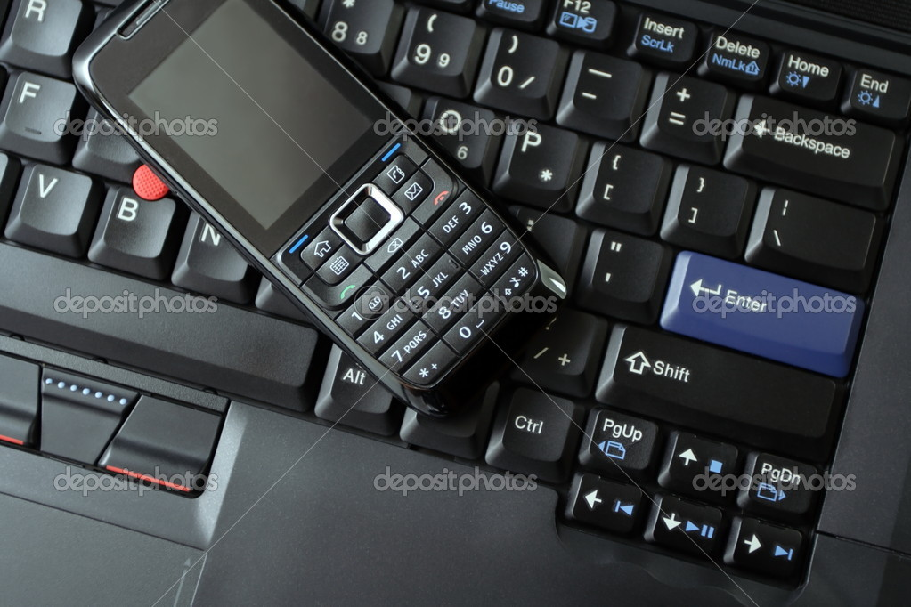 Neat and clean mobile phone on black laptop keyboard as a wireless technology concept. — Stock Photo #2376961