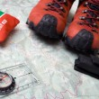 Hiking shoes and equipment on map — Stock Photo