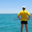 Men in yellow t-shirt near sea — Stock Photo #1624269